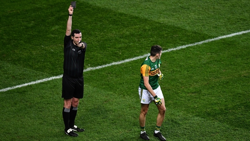 Referee Seán Hurson shows a black card to Graham O'Sullivan of Kerry