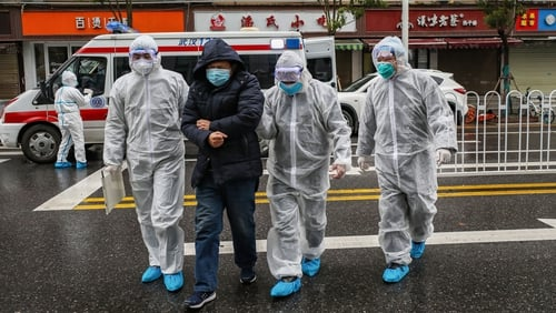 Medical workers escort a patient to hospital in Wuhan
