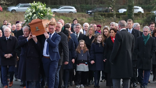 The coffin is carried into St James' Church
