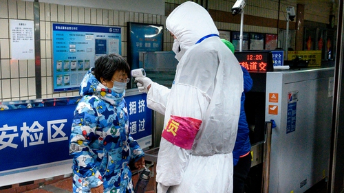 A passenger's temperature is checked at the entrance of subway station in Beijing