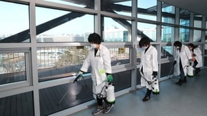 Quarantine officials spray disinfectant in a hallway at a government complex in South Korea