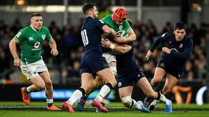 Josh van der Flier of Ireland is tackled by Adam Hastings (L) and Rory Sutherland of Scotland