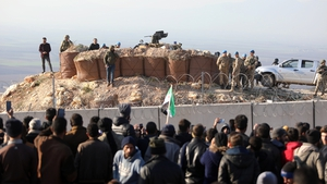 Syrian people gather near the Syrian-Turkish border