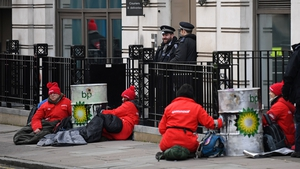 Greenpeace activists sit chained into oil barrels as they protest outside the headquarters of oil giant BP in London
