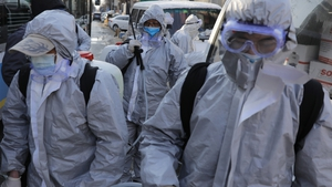 Workers wearing protective suits gather after they disinfected a residential area in Beijing