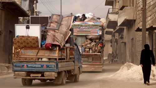 Vehicles carrying displaced people and their belongings drive through the town of Darret Ezza, northwest of Aleppo