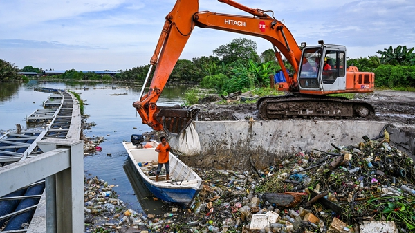 Workers clearing mounds of floating plastic waste on the Klang river on the outskirts of Kuala Lumpur