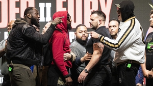 Deontay Wilder and Tyson Fury gesture after pushing each other on stage prior to their last press conference before their rematch in Las Vegas on Sunday morning