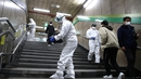Workers spray disinfectant at a metro station in Seoul