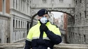 A police officer wears a respiratory mask in Venice