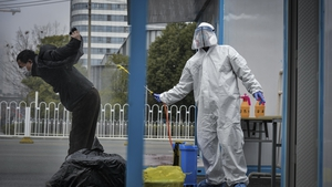 A worker disinfects a recovered COVID-19 patient departing a temporary hospital in Wuhan