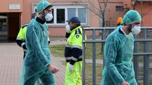 People wear protective face masks in front of a closed elementary school in Vo' Euganeo, Padua, Italy