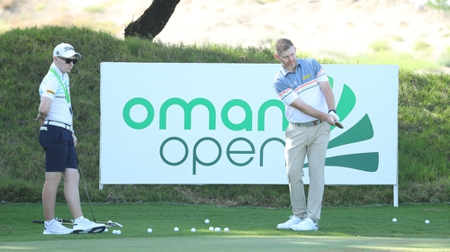 Stephen Gallacher of Scotland practices watched by his son and caddie Jack at the Oman Open