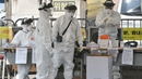 Medical personnel check drivers at a 'drive-through' virus test facility in Goyang, north of Seoul