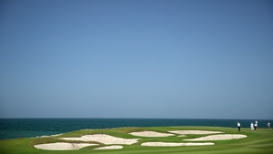 Competitors putt on the ninth green during the third round of the Oman Open at Al Mouj Golf