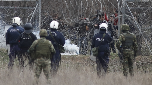 Police try to hold back migrants attempting to cross the border in Kastanies, Greece