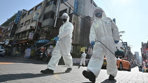 South Korean soldiers wearing protective gear spray disinfectant on a street in Seoul