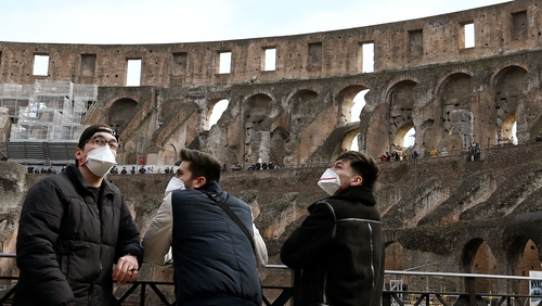 Tourists wear face masks as they visit the Colosseum in Rome