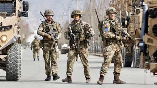 British soldiers stand guard at the site where a gunman opened fire