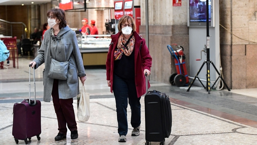 Passengers wearing protective face masks at Milano Centrale railway station
