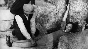 1930: A girl lies flat on the ground, in order to kiss the Blarney Stone in Blarney Castle, Cork city. Photo: Getty.