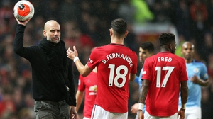 Pep Guardiola hands the ball to Bruno Fernandes during the Manchester derby