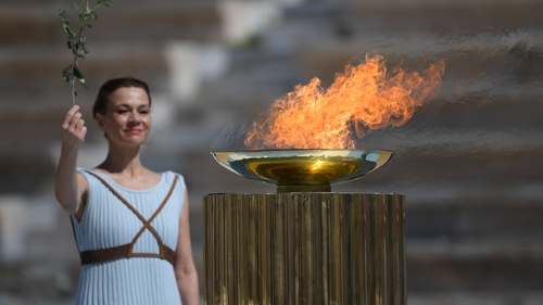 A perfomer stands next to the Olympic flame during the handover ceremony for the 2020 Tokyo Summer Olympics