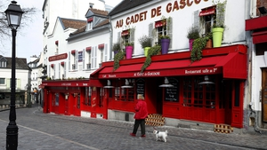 A woman walks her dog on a deserted street in Montmartre in Paris