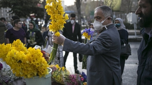 A man wears a face mask in Tehran, Iran while buying flowers ahead of Nowruz celebrations