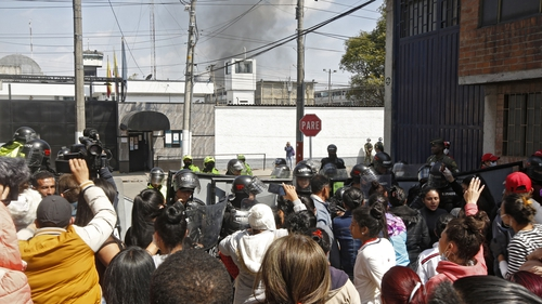 Relatives of inmates, journalists and riot police gather outside as smoke rises from the Modelo prison in Bogota