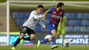 Newcastle Jets' Wes Hoolahan is pursued by Adrian Luna of Melbourne City