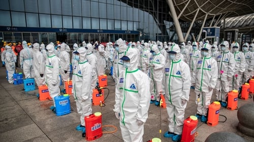 Staff members line up as they prepare to spray disinfectant at Wuhan Railway Station