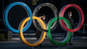 People wearing masks pose for photos next to the Olympic rings in Tokyo earlier today