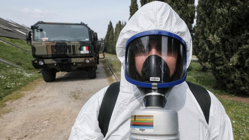 An Italian soldier wearing a protective suit helps in the transportation of coffins on military trucks from the Bergamo area