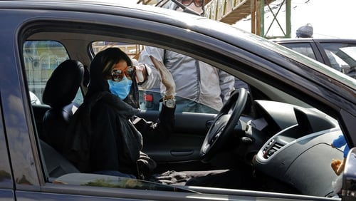 A woman is tested for coronavirus outside Tehran in Iran