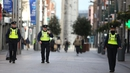 Gardaí patrol a near-deserted Henry Street in Dublin city centre today