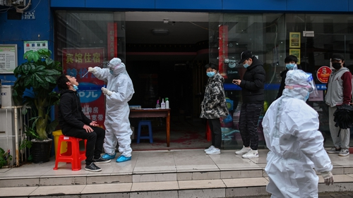 People wait in line to be tested for Covid-19 in Wuhan
