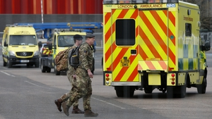 Military personnel stand near London Ambulance Service vehicles at the new NHS Nightingale Hospital at ExCeL London