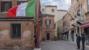 Carabinieri raise the flag at half-mast to remember people dying of the coronavirus in Venice today