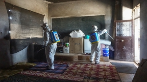 Members of the Syrian civil defence disinfect a former school building currently inhabited by displaced families in Binnish in Syria