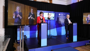 Arlene Foster and Michelle O'Neill with two interpreters on screen