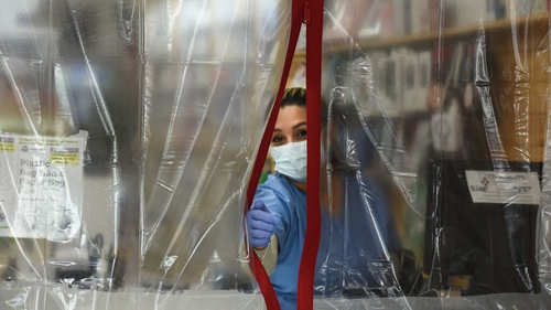 A pharmacist works behind plastic sheeting while wearing protective equipment in the Elmhurst area of New York City