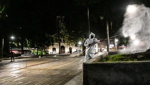 A police officer wearing protective clothing disinfects a park in Colombia