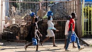 People carry supplies on the streets of Bulawayo, Zimbabwe