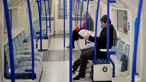 Two people, one wearing a face mask as a precautionary measure, sit on an empty London underground tube carriage