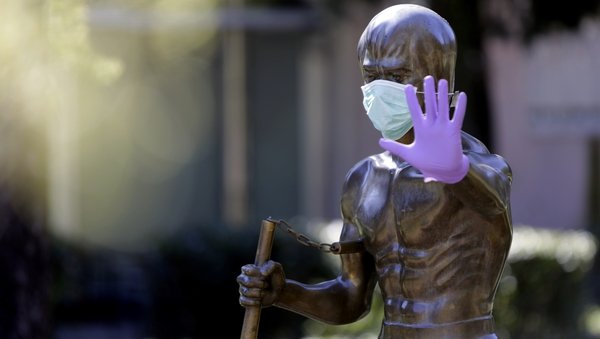 A statue dedicated to martial arts icon Bruce Lee, wearing surgical gloves and a face mask, in Bosnia