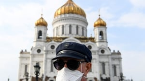 A person wearing a protective face mask stands in front of the Christ the Savior Cathedral in Moscow