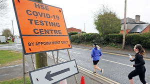 Runners pass a Covid-19 testing centre in Newbridge earlier this month. Photo: Niall Carson/PA Wire