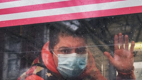 A man waves from a bus in a neighborhood in the Queens borough, which has one of the highest infection rates of coronavirus in the United States