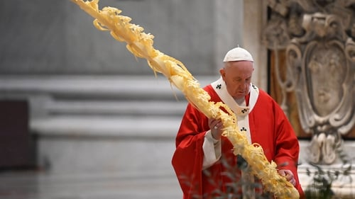 Pope Francis gathers his thoughts while holding a palm branch as he celebrates Palm Sunday
